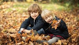 twee kinderen zitten in herfstbladeren