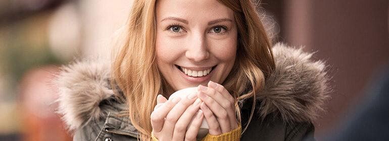 Jeune femme qui porte une veste se réchauffe avec une tasse – garantie accidents de la vie et protection cambriolage durant les mois d'automne et d'hiver